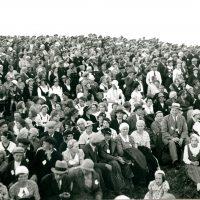 Mustavalkoinen kuva jossa iso joukko ihmisiä istumassa juhannusjuhlissa